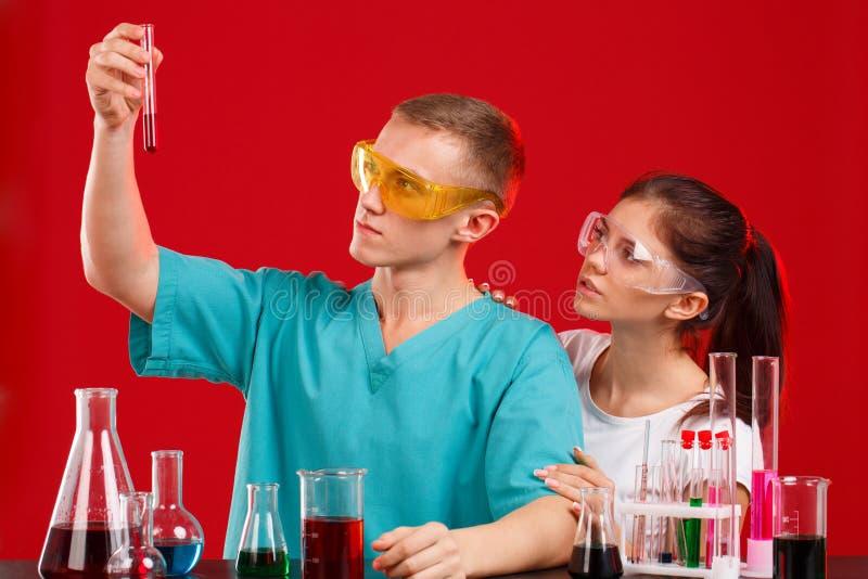 Δύο τεχνικοί εργαστηρίων εξετάζουν μια φιάλη με ένα κόκκινο υγρό Σε μια κόκκινη ανασκόπηση στοκ εικόνα