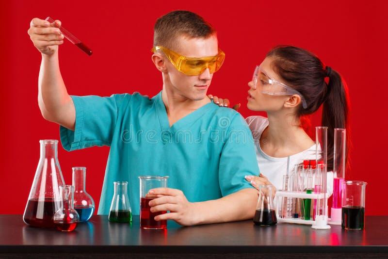 Δύο τεχνικοί εργαστηρίων σε ομοιόμορφο, εξετάζοντας ο ένας τον άλλον, ένας τύπος που κρατά ένα κόκκινο υγρό σε μια διαφανή φιάλη στοκ εικόνα