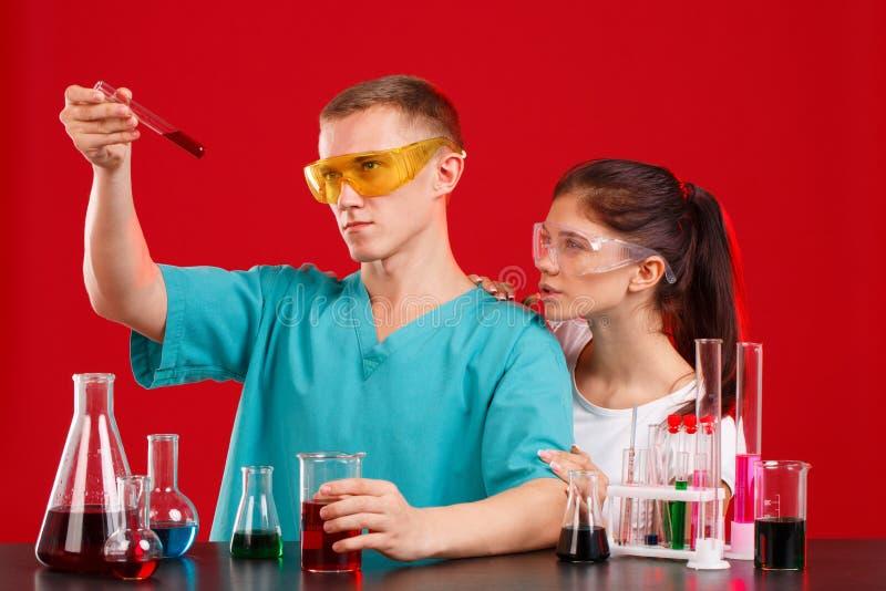 Δύο τεχνικοί εργαστηρίων σε ομοιόμορφο και τα γυαλιά εξετάζουν το κόκκινο υγρό σε μια διαφανή φιάλη Σε μια κόκκινη ανασκόπηση στοκ εικόνα