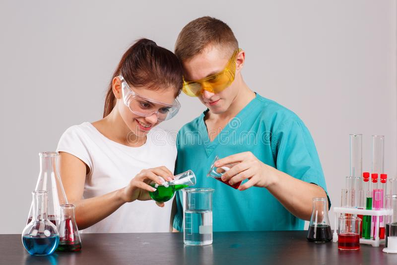 Δύο τεχνικοί εργαστηρίων χύνουν έξω το κόκκινο και πράσινο υγρό από δύο φιάλες σε μια κούπα στοκ εικόνα με δικαίωμα ελεύθερης χρήσης