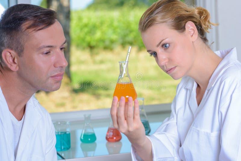 Δύο τεχνικοί που εξετάζουν το υγρό στη φιάλη γυαλιού στοκ εικόνες