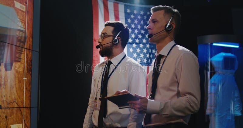 Δύο τεχνικοί που προσέχουν την οθόνη στο θάλαμο ελέγχου στοκ εικόνα με δικαίωμα ελεύθερης χρήσης
