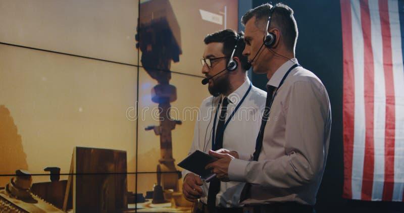 Δύο τεχνικοί που προσέχουν την οθόνη στο θάλαμο ελέγχου στοκ φωτογραφίες με δικαίωμα ελεύθερης χρήσης