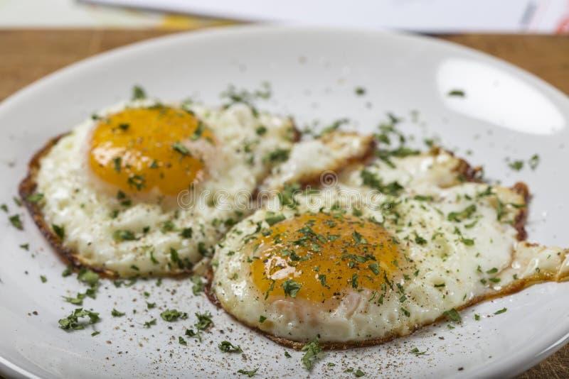 Δύο τηγανισμένα αυγά στο άσπρο πιάτο με το αλατισμένο και μαύρο πιπέρι στοκ εικόνες