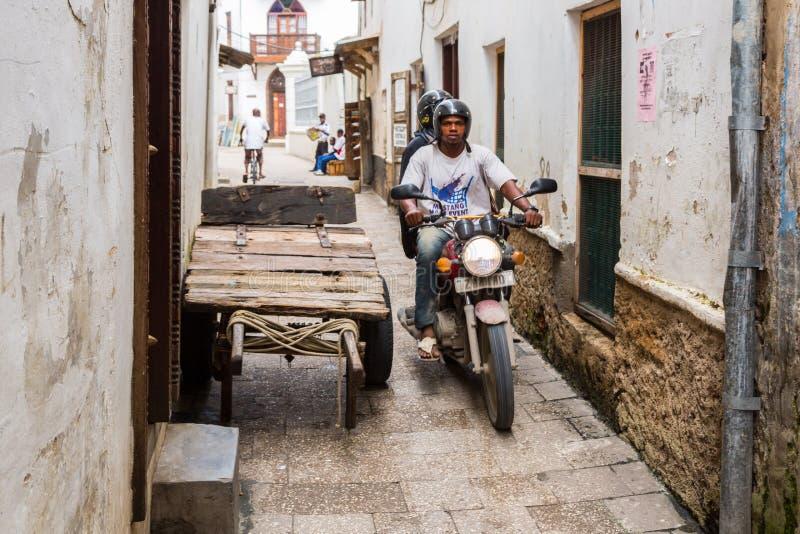 Δύο τοπικά άτομα που οδηγούν μια μοτοσικλέτα μέσω των στενών οδών της πέτρινης κωμόπολης, παλαιό αποικιακό κέντρο της πόλης Zanzi στοκ εικόνα με δικαίωμα ελεύθερης χρήσης
