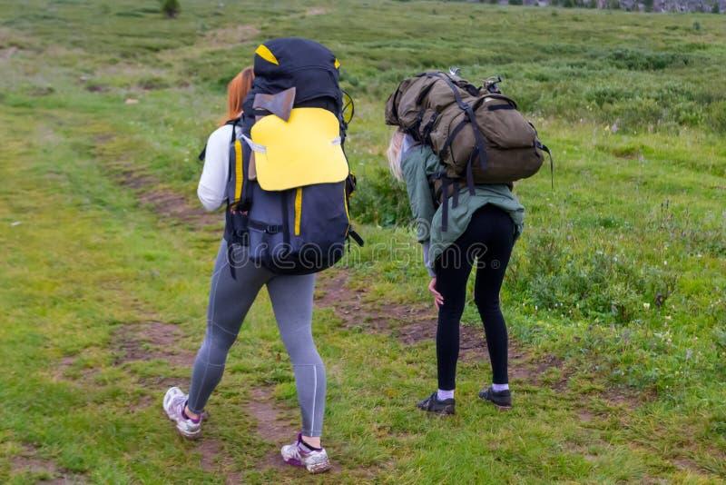 Δύο τουρίστες κοριτσιών με τα σακίδια πλάτης πηγαίνουν στο δρόμο που καλύπτεται με το ST στοκ φωτογραφία με δικαίωμα ελεύθερης χρήσης