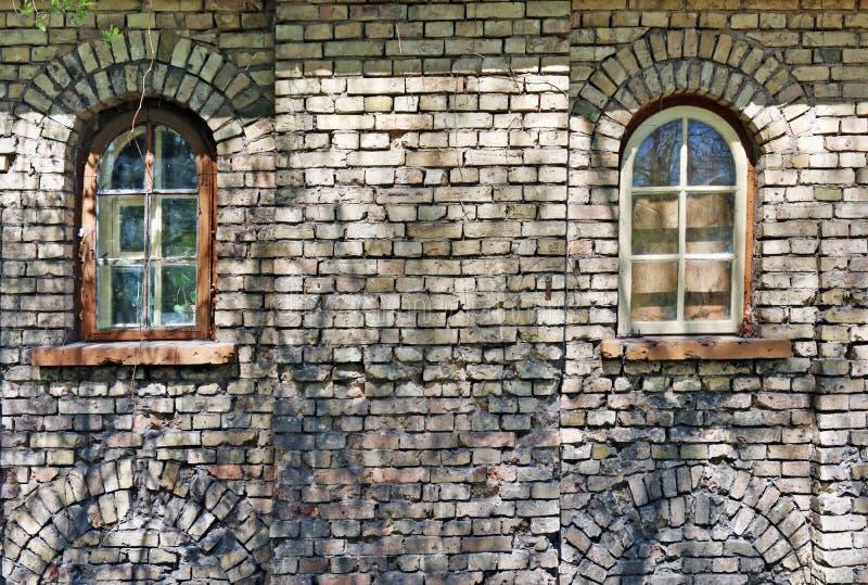Δύο τυφλά παράθυρα στον κίτρινο τουβλότοιχο της μεγάλης ηλικίας στοκ φωτογραφία με δικαίωμα ελεύθερης χρήσης