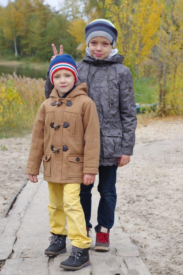 Δύο τυχεροί και χαμογελώντας αδελφοί στην πορεία φθινοπώρου, να φωνάξει κέρατα Πάρκο φθινοπώρου στοκ εικόνα