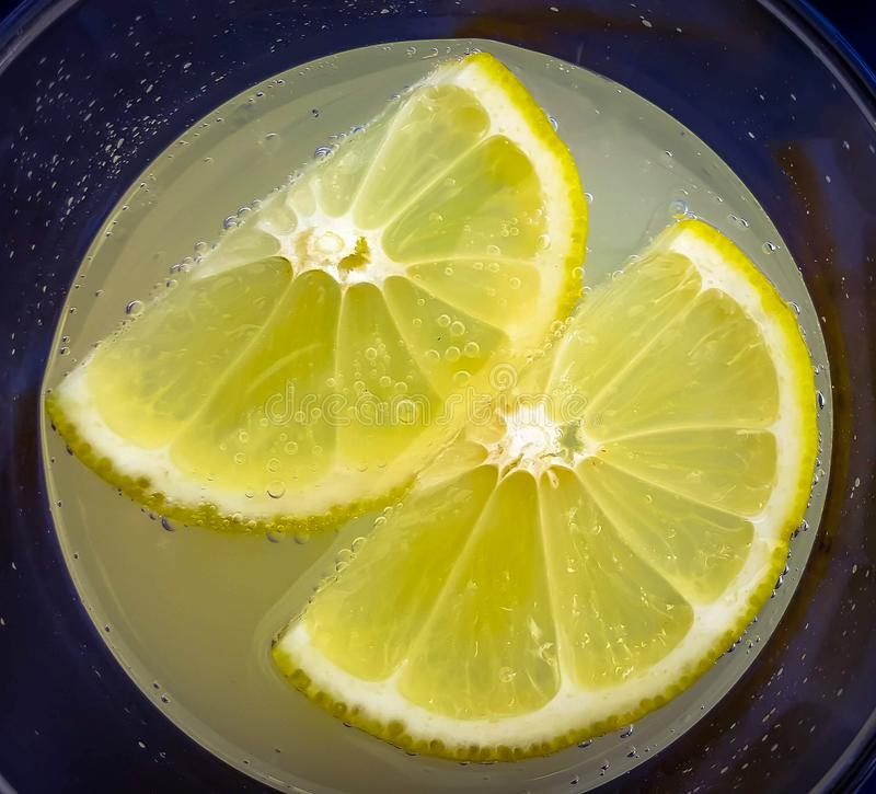 Δύο φέτες του λεμονιού σε ένα γυαλί με το μη οινοπνευματώδες ποτό στοκ φωτογραφία