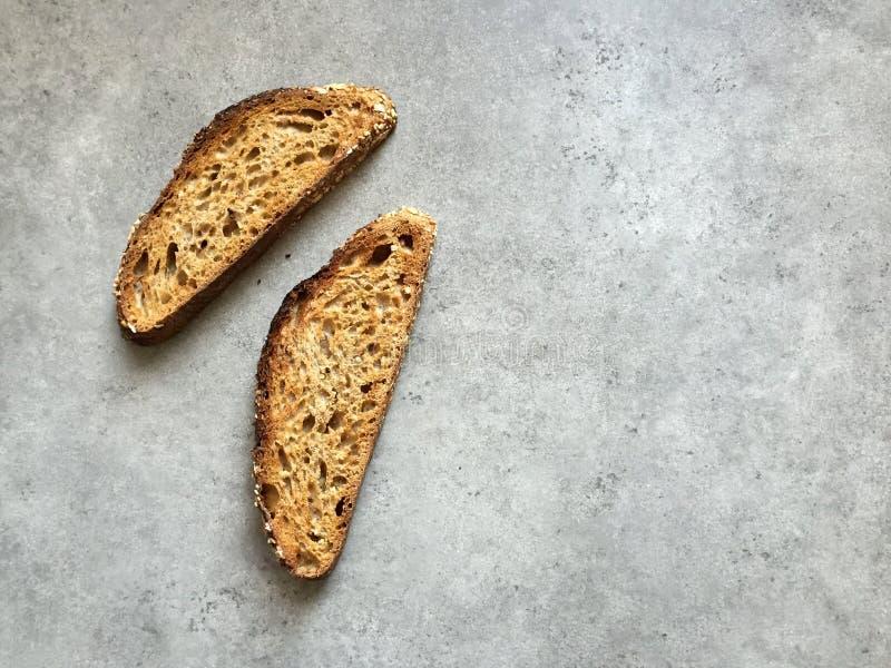 Δύο φέτες του χειρωνακτικού ψωμιού σίτου μαγιάς ολόκληρου γκρίζο countertop στοκ εικόνες