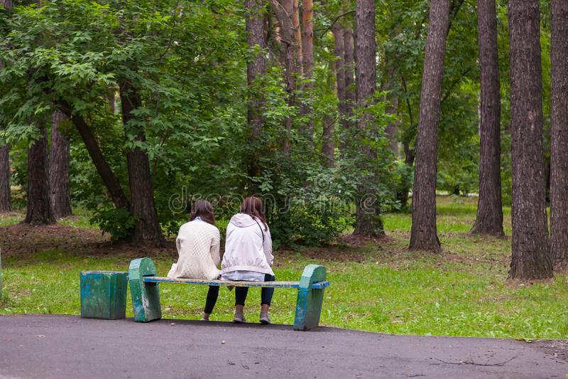 Δύο φίλες κοριτσιών κάθονται σε έναν παλαιό ξύλινο πάγκο σε ένα πάρκο πόλεων και εξετάζουν τα έτη με τα πράσινα δέντρα συζητώντας στοκ φωτογραφία