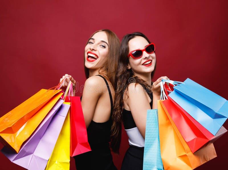 Δύο φίλες που κρατούν πολλές ζωηρόχρωμες τσάντες αγορών εγγράφου στοκ φωτογραφία με δικαίωμα ελεύθερης χρήσης