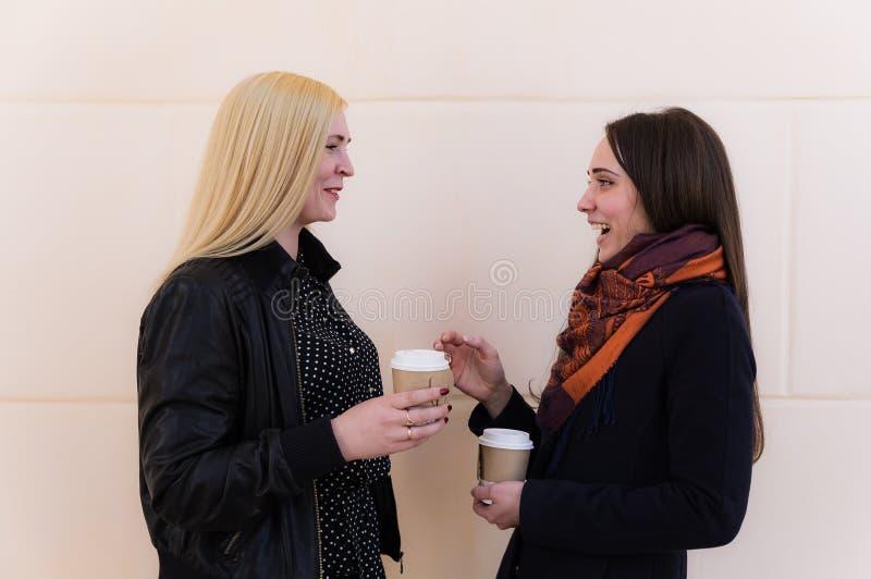 Δύο φίλες που κρατούν τα φλυτζάνια και το κουτσομπολιό εγγράφου στοκ φωτογραφία