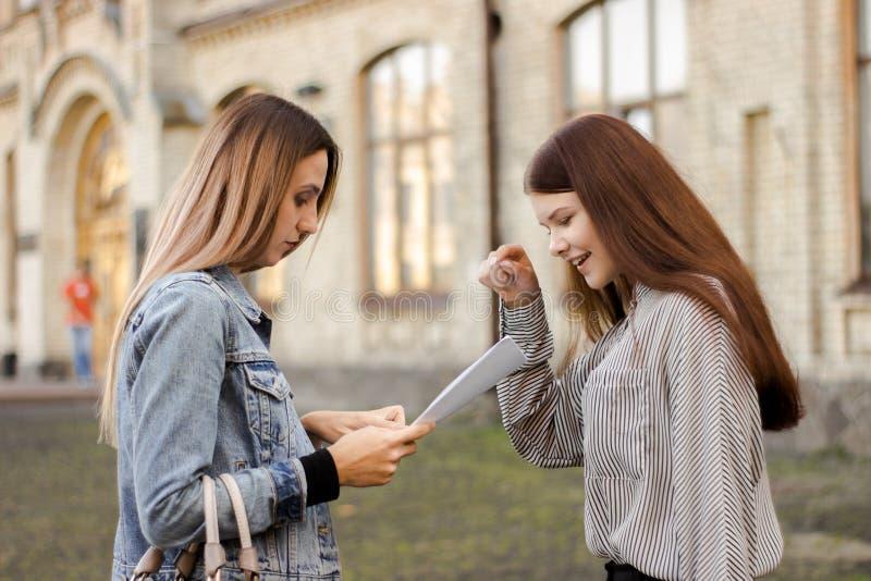 Δύο φίλες στέκονται κοντά στο πανεπιστήμιο και εξετάζουν τα έγγραφα στοκ φωτογραφία με δικαίωμα ελεύθερης χρήσης