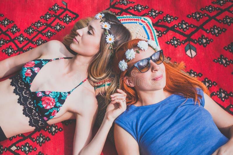 Δύο φίλες χίπηδων που στηρίζονται στην κουβέρτα έξω στοκ φωτογραφία με δικαίωμα ελεύθερης χρήσης