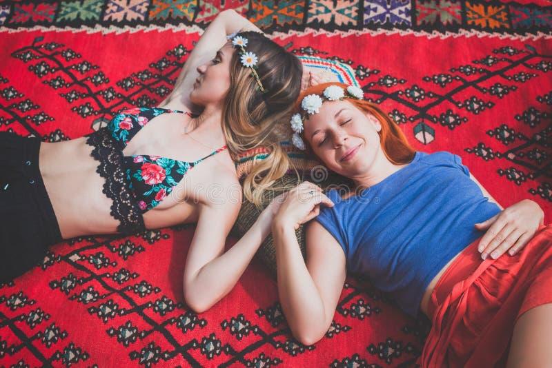 Δύο φίλες χίπηδων που στηρίζονται στην κουβέρτα έξω στοκ εικόνα