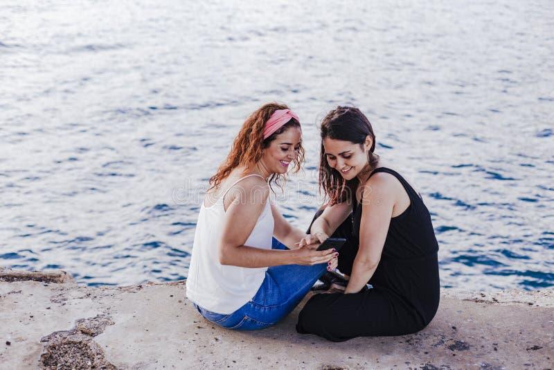 Δύο φίλοι γυναικών που κάθονται από την παραλία που χρησιμοποιεί το κινητό τηλέφωνο και το χαμόγελο Έννοια τεχνολογίας και τρόπου στοκ εικόνες
