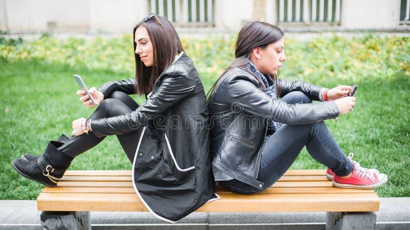 Δύο φίλοι κοριτσιών που χρησιμοποιούν τα κινητά τηλέφωνα στον πάγκο πάρκων στοκ εικόνες