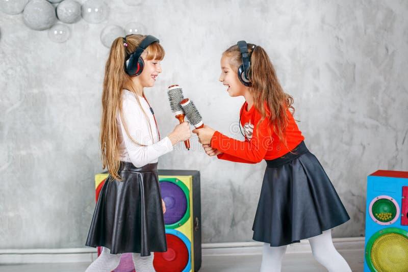 Δύο φίλοι μικρών κοριτσιών τραγουδούν και χορεύουν Η έννοια είναι παιδική ηλικία στοκ φωτογραφίες με δικαίωμα ελεύθερης χρήσης