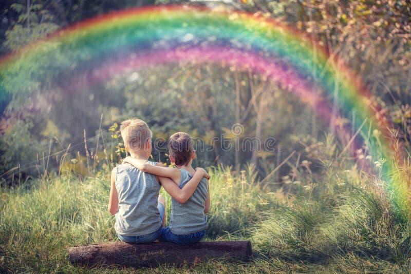 Δύο φίλοι μικρών παιδιών που κρατούν και που απολαμβάνουν τη φύση με το ουράνιο τόξο στην ηλιόλουστη θερινή ημέρα στοκ εικόνες με δικαίωμα ελεύθερης χρήσης
