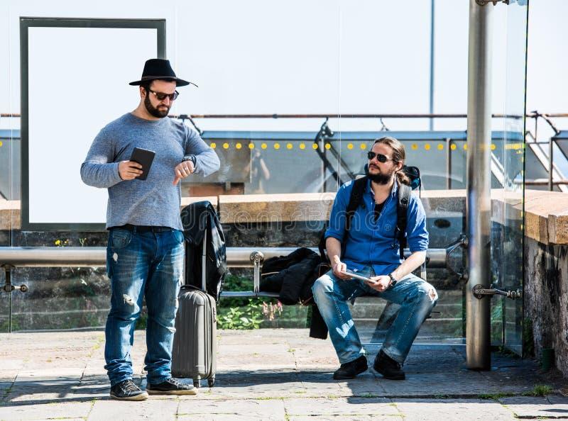 Δύο φίλοι περιμένουν και παίρνουν τρελλοί λόγω της καθυστέρησης στοκ φωτογραφία
