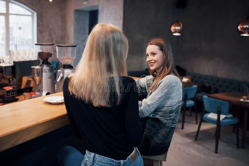 Δύο φίλοι που απολαμβάνουν τον καφέ μαζί σε μια καφετερία όπως κάθονται επιτραπέζια να κουβεντιάσουν στοκ φωτογραφίες