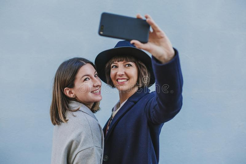 Δύο φίλοι υπαίθρια με τα μοντέρνα ενδύματα που παίρνουν ένα selfie με το κινητό τηλέφωνο lifestyle στοκ εικόνα