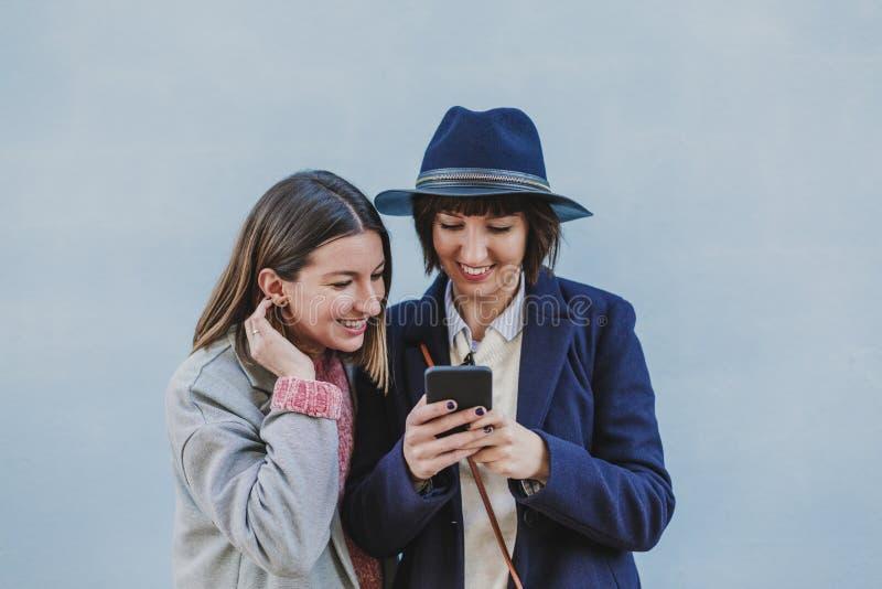Δύο φίλοι υπαίθρια με τα μοντέρνα ενδύματα που παίρνουν ένα selfie με το κινητό τηλέφωνο lifestyle στοκ φωτογραφίες