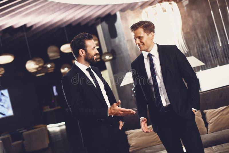 """Δύο φίλοι χαμογελάνε ενώ μιλούσαν στο χολ Ï""""Î¿Ï… ξενοδοχείου στοκ φωτογραφίες με δικαίωμα ελεύθερης χρήσης"""