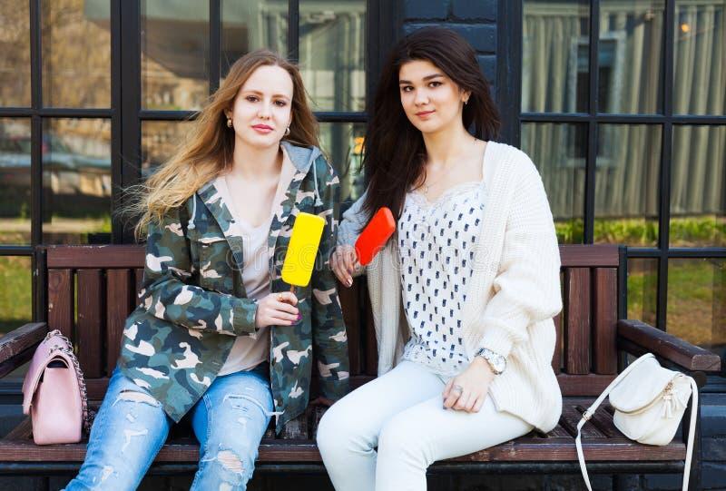 Δύο φίλες κοριτσιών που ντύνονται στο υπόλοιπο εξαρτήσεων μόδας, τρώνε το παγωτό eskimo στοκ εικόνες με δικαίωμα ελεύθερης χρήσης