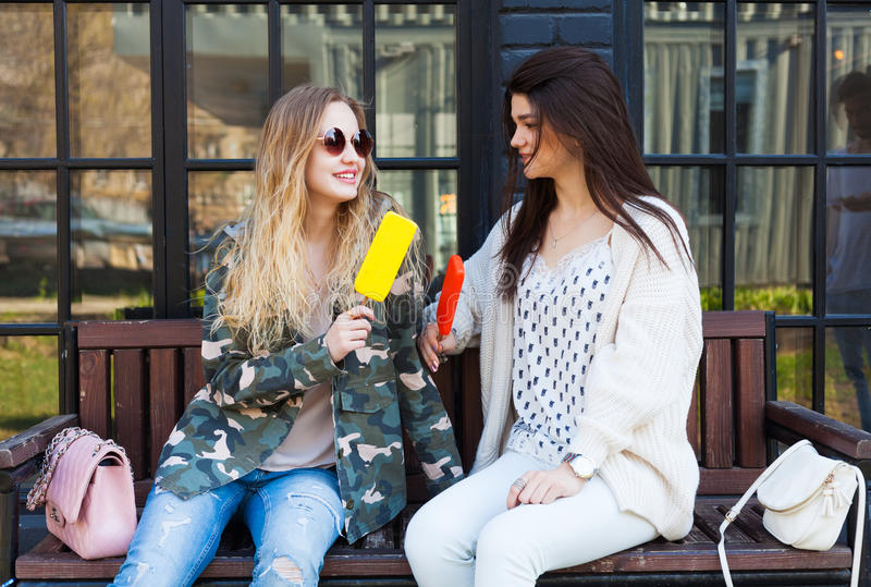 Δύο φίλες κοριτσιών που ντύνονται στο υπόλοιπο εξαρτήσεων μόδας, τρώνε το παγωτό στοκ εικόνα