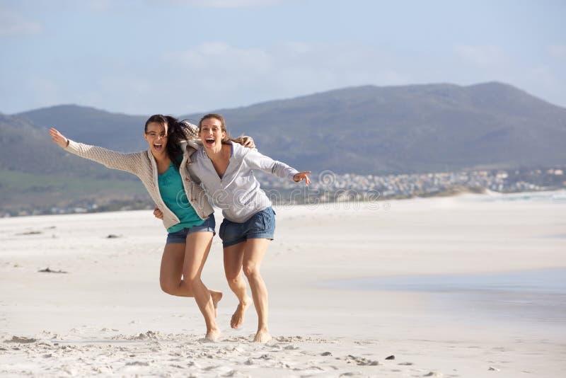 Δύο φίλες που γελούν στην παραλία στοκ εικόνα