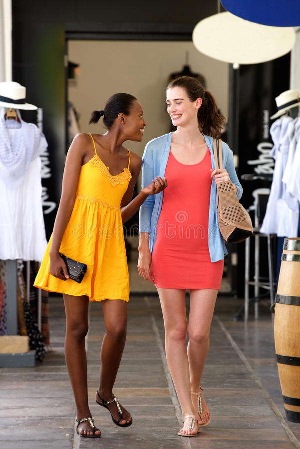 Δύο φίλες που περπατούν και που μιλούν στη λεωφόρο αγορών στοκ φωτογραφίες
