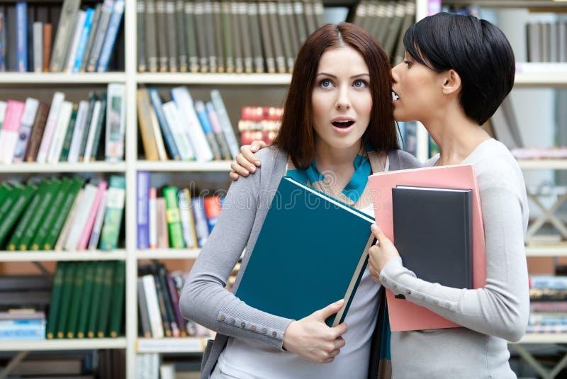 Δύο φίλες ψιθυρίζουν στη βιβλιοθήκη στοκ φωτογραφία