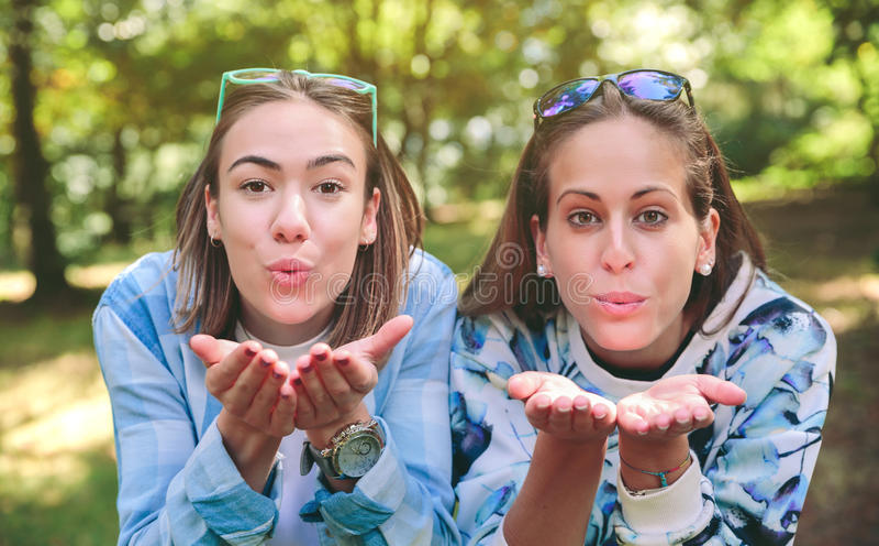 Δύο φίλοι γυναικών που φυσούν το φιλί στη κάμερα στοκ φωτογραφίες