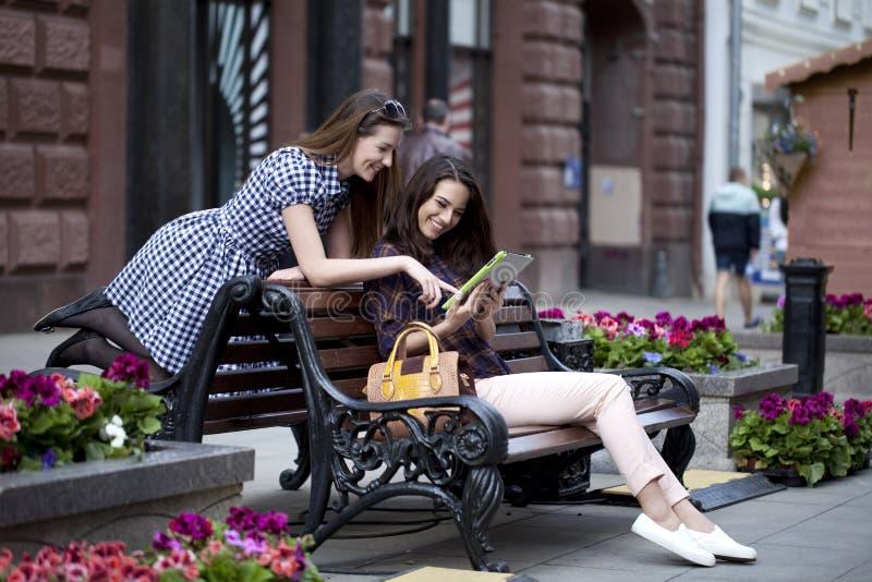 Δύο φίλοι κοριτσιών που κάθονται σε έναν πάγκο στο πόλης κέντρο στοκ εικόνα με δικαίωμα ελεύθερης χρήσης