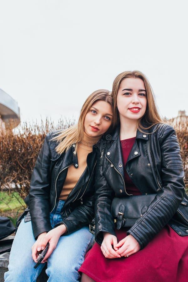Δύο φίλοι νέων κοριτσιών που κάθονται μαζί και που έχουν τη διασκέδαση υπαίθρια lifestyle στοκ εικόνες με δικαίωμα ελεύθερης χρήσης