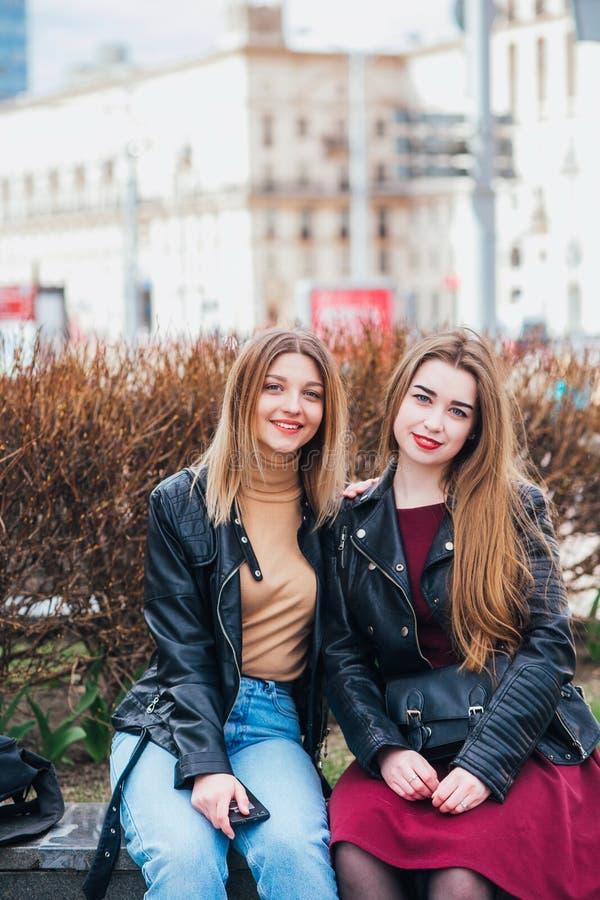 Δύο φίλοι νέων κοριτσιών που κάθονται μαζί και που έχουν τη διασκέδαση υπαίθρια lifestyle στοκ φωτογραφίες με δικαίωμα ελεύθερης χρήσης