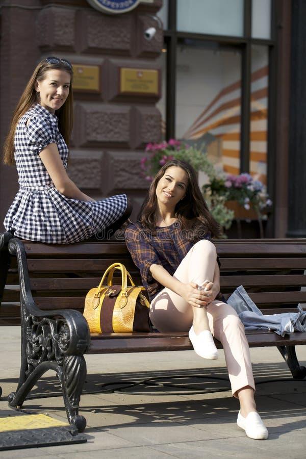 Δύο φίλοι νέων κοριτσιών που κάθονται στον πάγκο στο πόλης κέντρο στοκ φωτογραφία με δικαίωμα ελεύθερης χρήσης