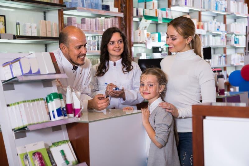 Δύο φαρμακοποιοί και πελάτες στοκ εικόνες