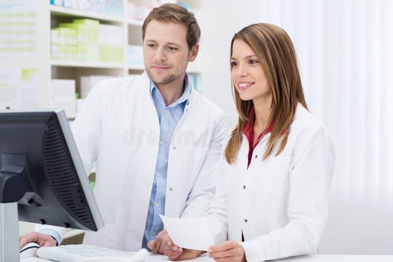 Δύο φαρμακοποιοί που εκπληρώνουν μια συνταγή στοκ εικόνες
