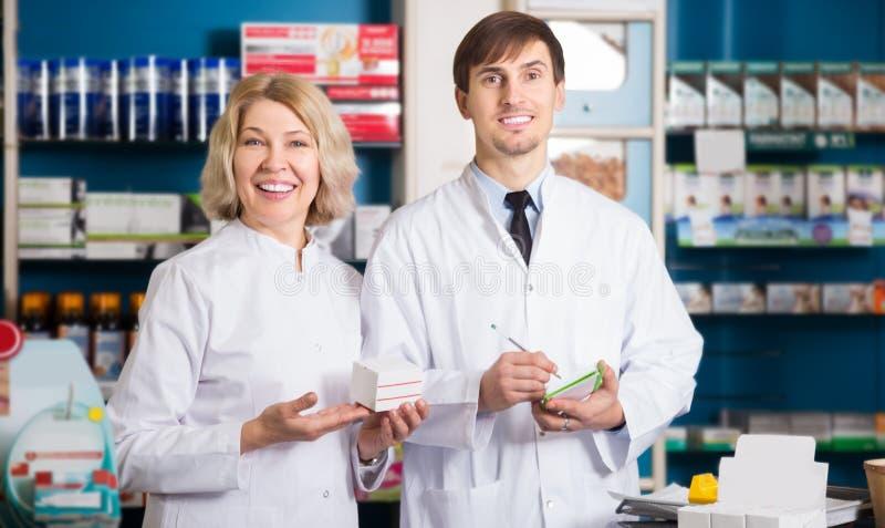 Δύο φαρμακοποιοί που θέτουν στο φαρμακείο στοκ εικόνες με δικαίωμα ελεύθερης χρήσης