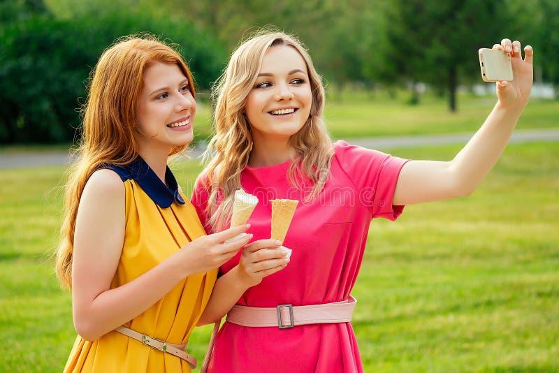 Δύο φιλενάδες όμορφη νεαρή κοκκινομάλλα με κίτρινο φόρεμα και ξανθιά γυναίκα με ροζ φόρεμα που τρώει στοκ φωτογραφία με δικαίωμα ελεύθερης χρήσης
