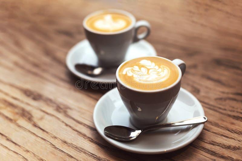 Δύο φλιτζάνια του καφέ στον ξύλινο πίνακα στοκ φωτογραφίες με δικαίωμα ελεύθερης χρήσης