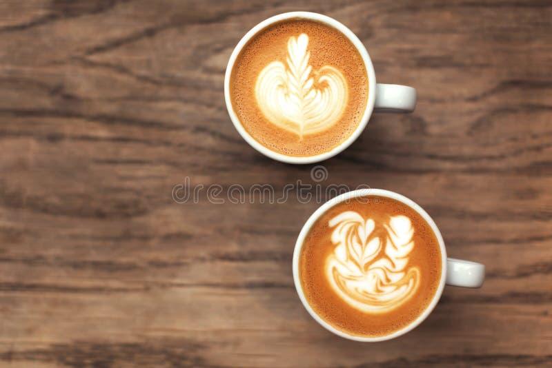 Δύο φλιτζάνια του καφέ στον ξύλινο πίνακα στοκ φωτογραφία με δικαίωμα ελεύθερης χρήσης