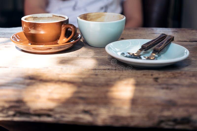 Δύο φλυτζάνια του καυτού καφέ και ενός πιάτου με το κουτάλι και δίκρανο στον εκλεκτής ποιότητας ξύλινο πίνακα με τους ανθρώπους στοκ φωτογραφία