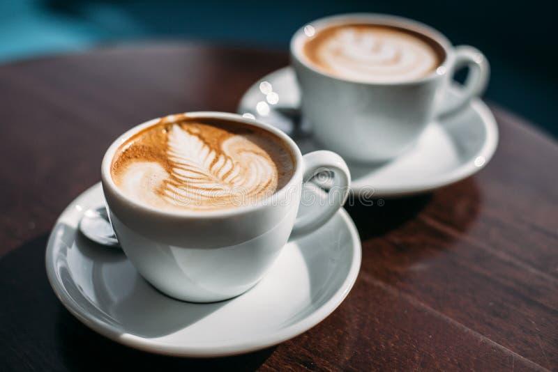 Δύο φλυτζάνια του cappuccino με την τέχνη latte στον ξύλινο πίνακα στοκ φωτογραφίες