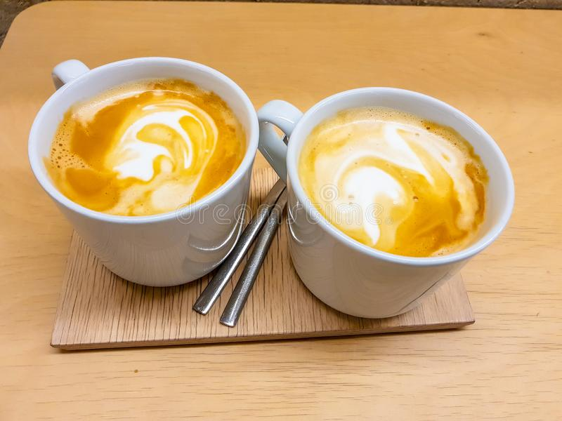 Δύο φλυτζάνια του latte με τις μορφές σχεδίων αφρού του Παρουσιασμένος σε έναν ξύλινο πίνακα στους πολύτιμους θερμούς τόνους στοκ φωτογραφίες με δικαίωμα ελεύθερης χρήσης