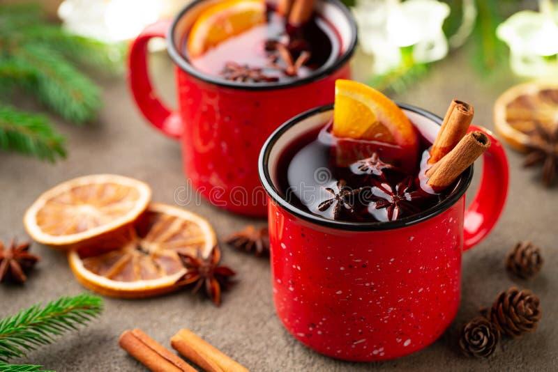 Δύο φλυτζάνια των Χριστουγέννων θέρμαναν το κρασί ή gluhwein με τα καρυκεύματα και τις πορτοκαλιές φέτες στην αγροτική άποψη επιτ στοκ εικόνες με δικαίωμα ελεύθερης χρήσης