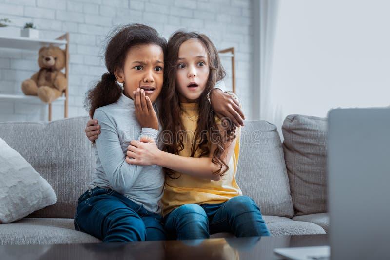 Δύο φοβησμένα κορίτσια που προσέχουν τη φρίκη στο lap-top στο σπίτι στοκ εικόνες